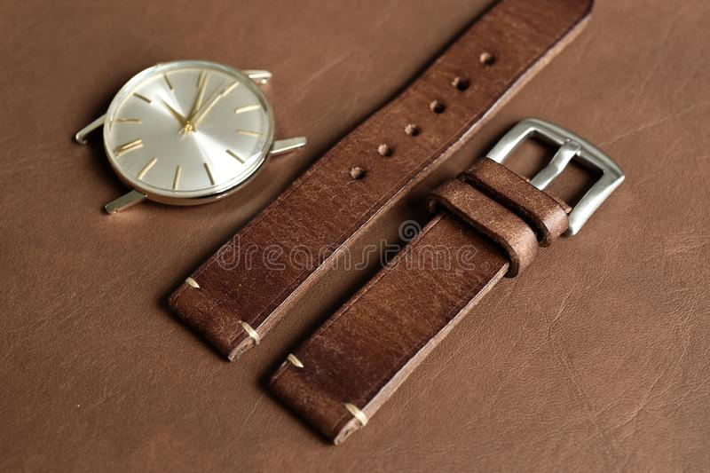 Dark brown leather watch strap with stainless buckle on leather background, Craft and handmade watch bracelet. Luxury classic and vintage style royalty free stock photos