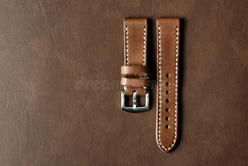 Dark brown leather watch strap with stainless buckle on leather background, Craft and handmade watch bracelet. Dark brown leather watch strap with stainless stock photos