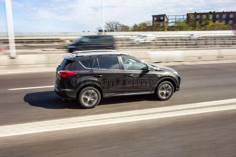 Dark brown SUV car driving fast on a highway with motion blur effect stock image