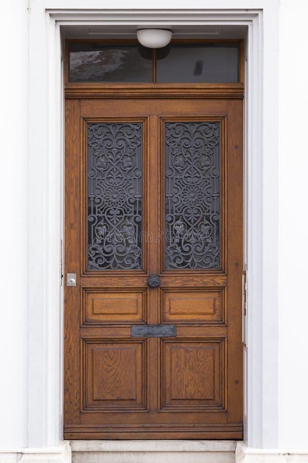 Dark brown wooden door with metal ornaments stock photos