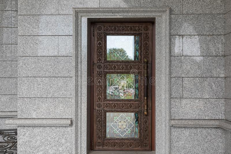 Dark brown wooden door with wood carving and tinted glass. Dark brown wooden door with woodcarving and colored glass stock image