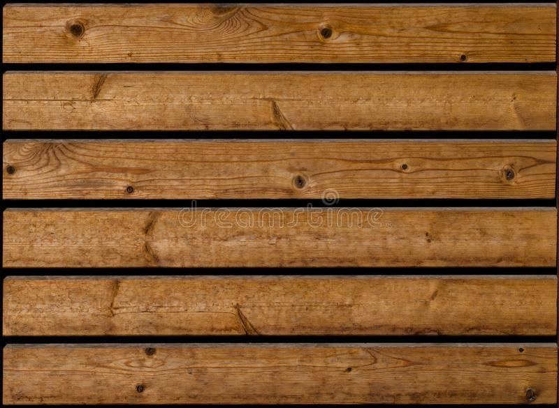 Dark brown wooden planks with black distance between them. Slightly worn up and with wooden knots. Seem like simple fence or wooden floor. Plank seems slightly stock images