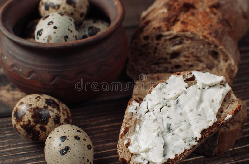 Dark buckwheat bread is spread with cottage cheese with herbs in a cut on a wooden table near quail eggs in a clay plate in a stock photography