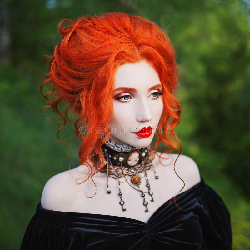 Dark carnival attire. Vampire woman with pale skin and red hair in black edwardian gown and renaissance bracelet on hand. royalty free stock photos