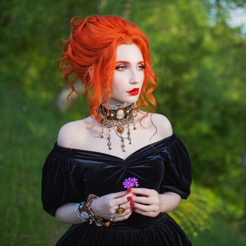 Dark carnival attire. Witch woman with pale skin and red hair in black fairytale gown and renaissance bracelet on hand. Pronounces spell. Gothic look. Fairytale royalty free stock photography