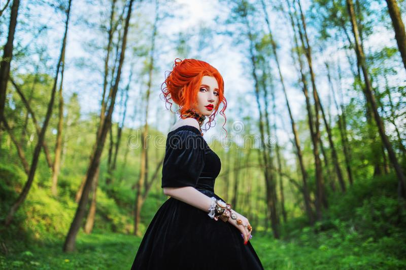 Dark carnival attire. Witch woman with pale skin and red hair in black mystical gown and renaissance bracelet on hand pronounces s. Pell. Dark look. Mystical stock images