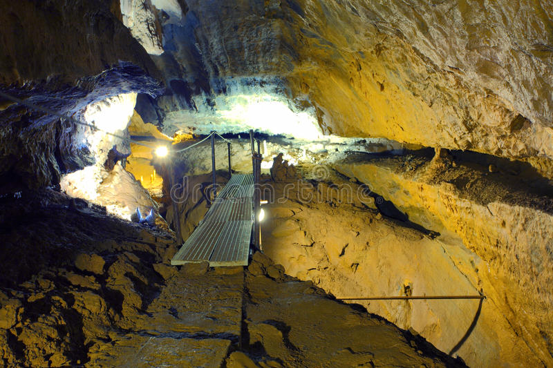 A dark cave with a pathway underground royalty free stock photos
