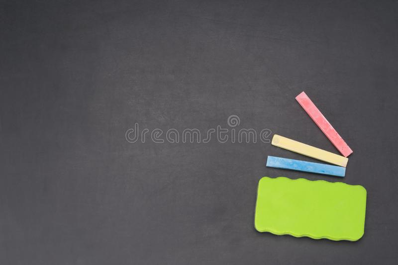 Dark chalk board with crayons and cleaning sponge royalty free stock photography