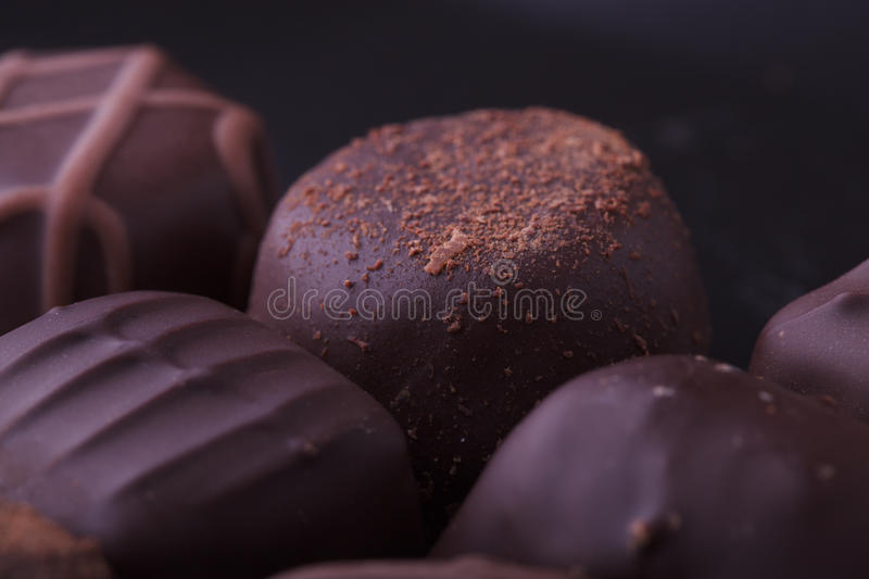 Dark Chocolate Pralines. Closeup of dark filled chocolate pralines from a selection box stock image