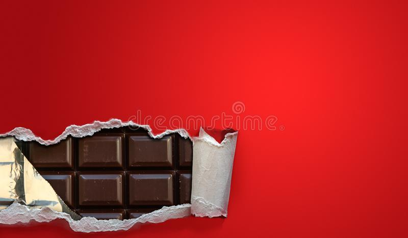 Dark chocolate bars in a red package strip open. Background with copy space royalty free stock photography