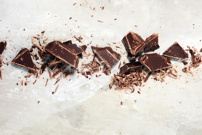 Dark chocolate bars on stone table and broken pieces of cocoa.  stock image