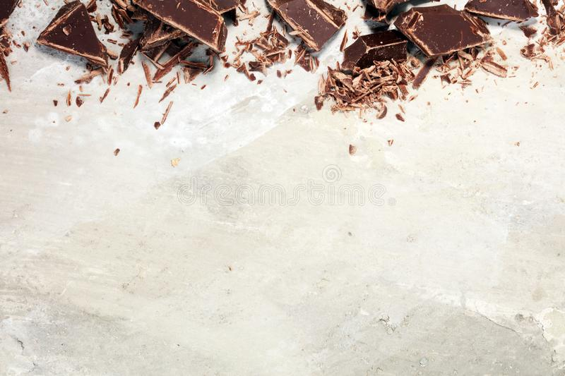 Dark chocolate bars on stone table and broken pieces of cocoa.  royalty free stock photography