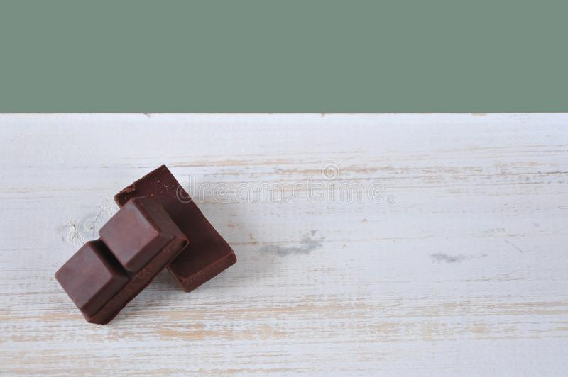 Dark Chocolate Bars on White Wooden with Copy Sapce. Dark chocolate bars on white wooden background with pastel green color for copy space royalty free stock photos