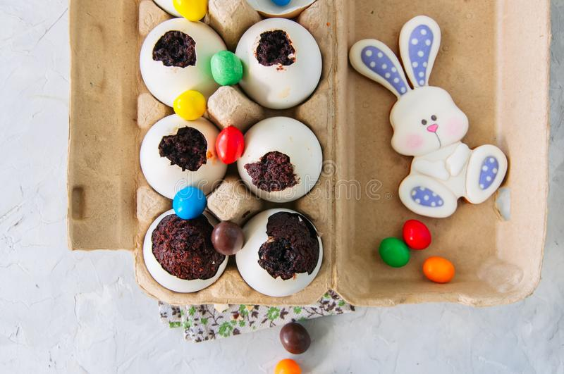 Dark chocolate brownie dessert in egg shells. Easter or funny kids party concept. White stone background. royalty free stock photography