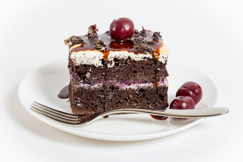 Dark chocolate cake with sweet cherry. On plate, white background stock image