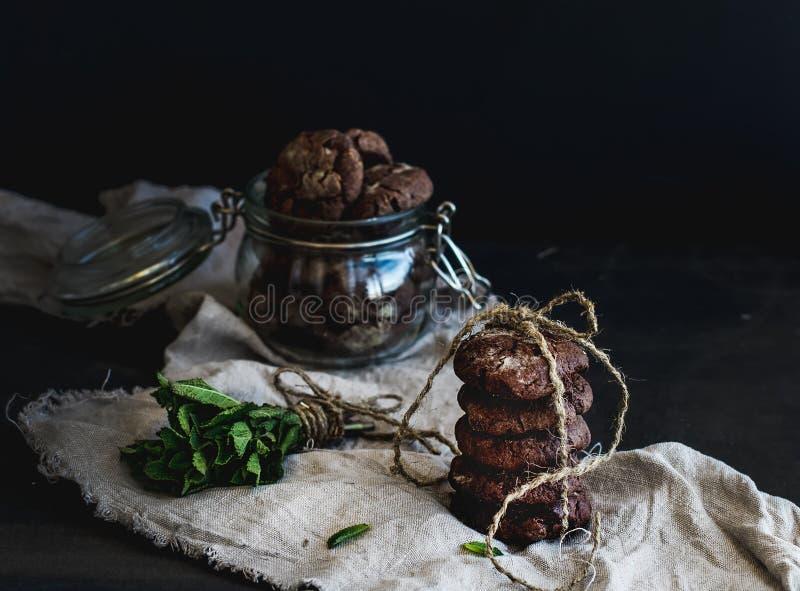 Dark chocolate chip cookies with fresh mint on dark backdrop stock photos