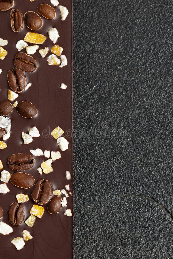 Dark chocolate with coffee grains and fruits on dark stone background. Prepared for the World Chocolate Day,. Photographed macro stock photo