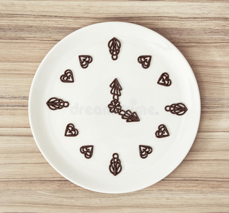 Dark chocolate garnishes in the shape of the clock stock image