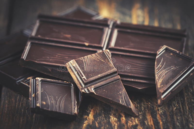 Dark chocolate over wooden backround with some cocoa powder stock image