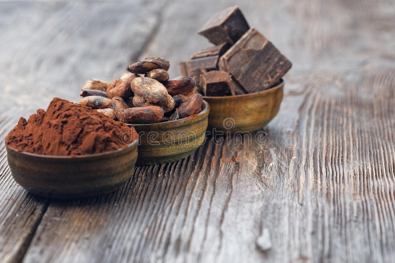 Dark chocolate pieces, cocoa powder and cocoa beans. On a wooden table royalty free stock photos
