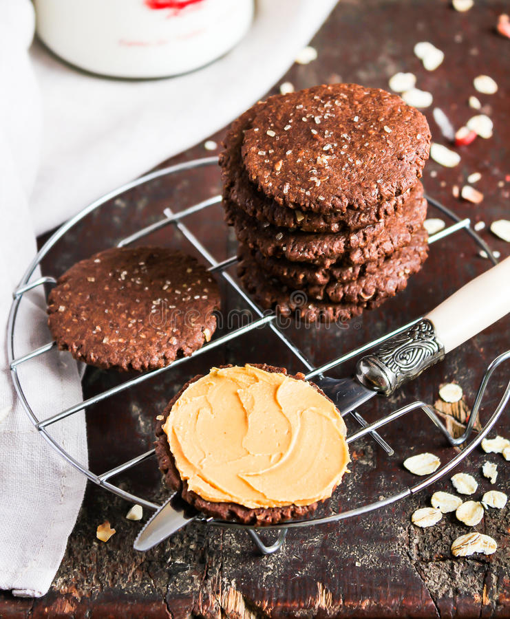 Dark chocolate sandwich cookies with oat flakes and peanut butter cream stacked on a cooling rack on a wooden table. Selective focus stock image