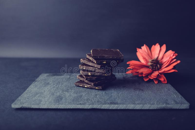 Dark chocolate on stone colored with red flower. Pieces of dark chocolate on stone. Appetizing and colorful. Just perfect for Valentines Day royalty free stock photos