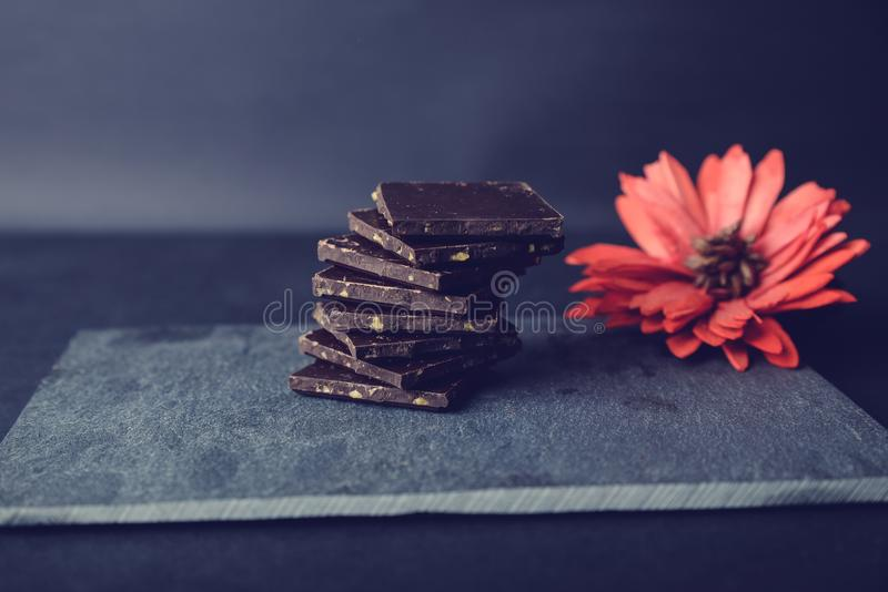 Dark chocolate on stone colored with red flower. Pieces of dark chocolate on stone. Appetizing and colorful. Just perfect for Valentines Day stock photos