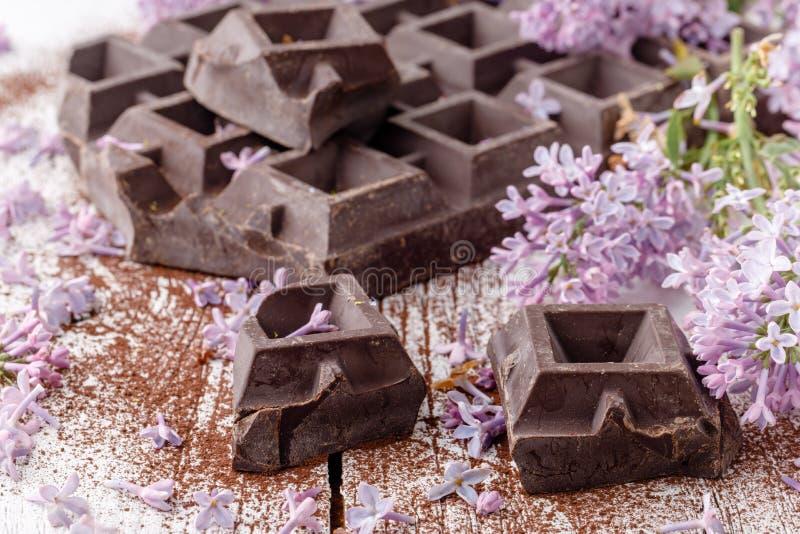 Dark chocolate on table with liliac flowers stock photo