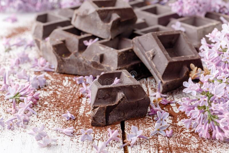 Dark chocolate on table with liliac flowers royalty free stock image
