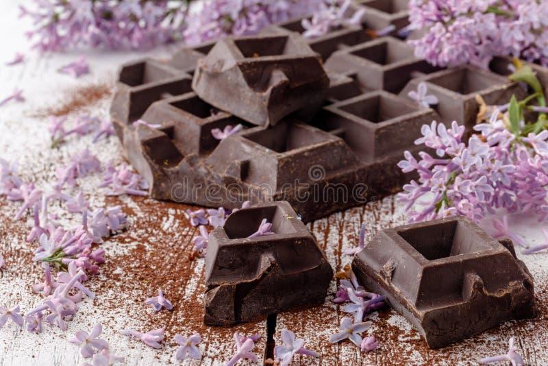 Dark chocolate on table with liliac flowers royalty free stock photos