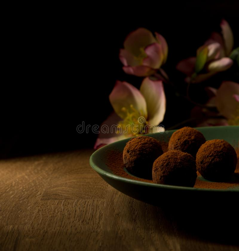 Dark chocolate truffles in green plate on wooden, and pink flowers in background. royalty free stock photo