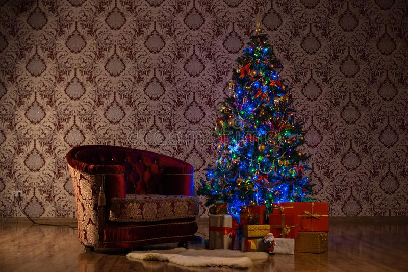 Dark Christmas scene with a lighted Christmas tree, gifts and armchair. Dark Christmas scene with a lighted Christmas tree, gifts and one armchair royalty free stock photos