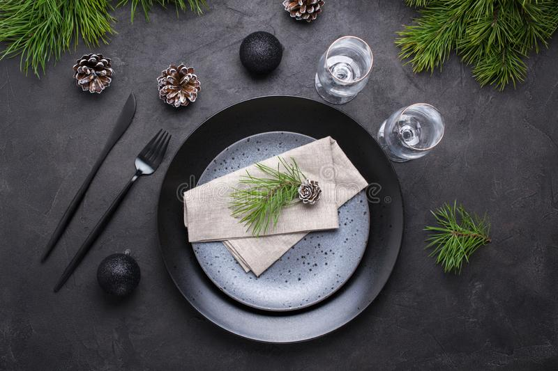 Dark christmas table setting design. Black plates, champagne glasses, fork and knife set with napkin, fir branch stock images