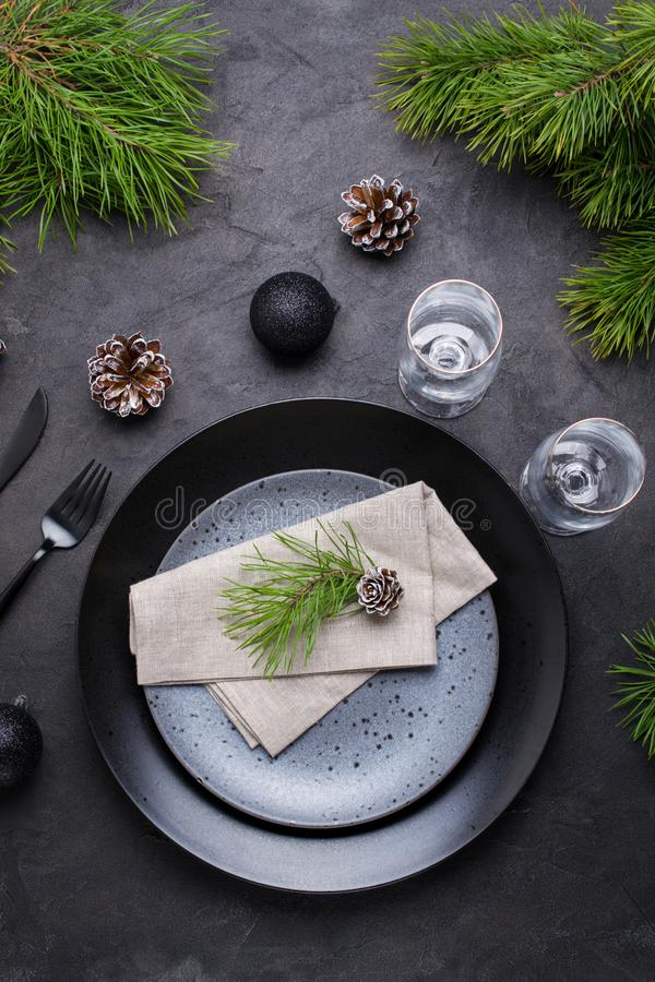 Dark christmas table setting design. Black plates, champagne glasses, fork and knife set with napkin, fir branch royalty free stock photography