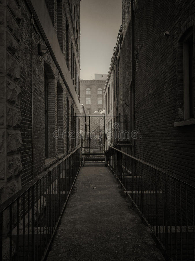 Dark city alley. With brick buildings and a metal walkway royalty free stock photography