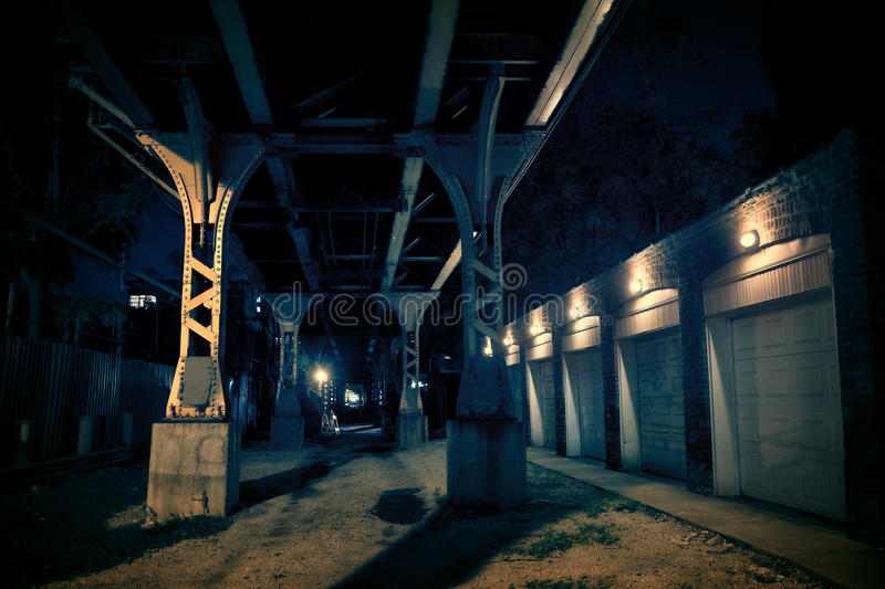 Dark City Alley at Night. Dark urban downtown city alley at night with car garage doors and elevated train tracks stock photo