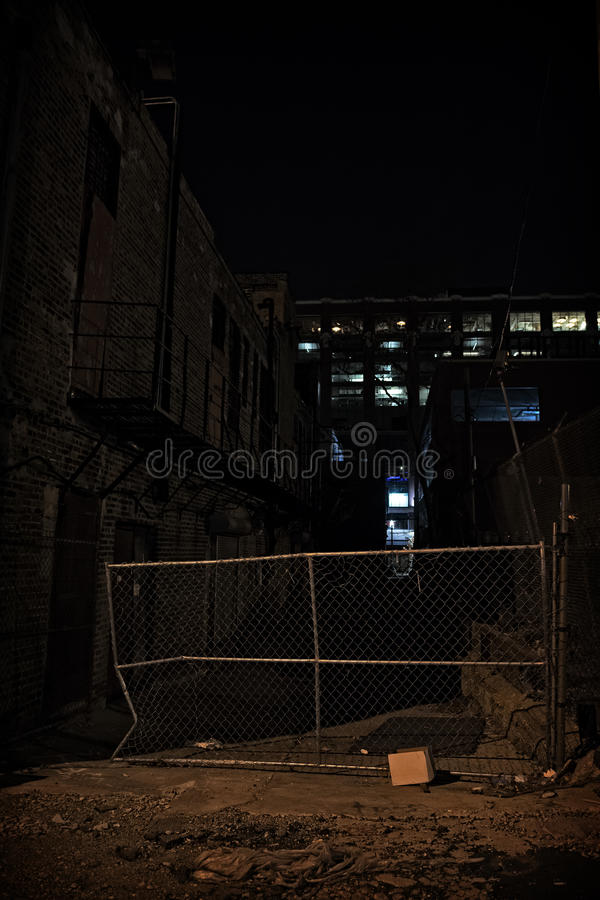 Dark City Alley at Night. Dark urban city alley with fence at night royalty free stock photography
