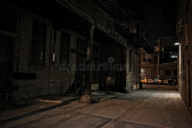 Dark City Alley at Night. Dark urban city alley at night with loading dock and cars stock photo