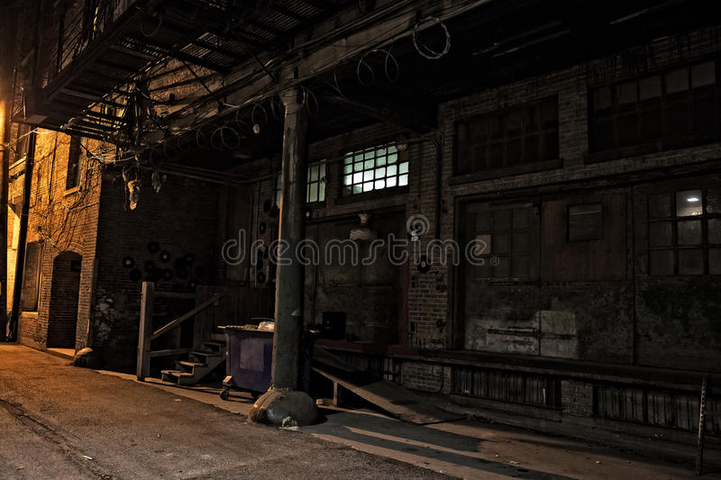 Dark City Alley at Night. Dark urban city alley at night with loading dock and dumpster. Interesting décor with vinyl records, dress and barb wire stock photo