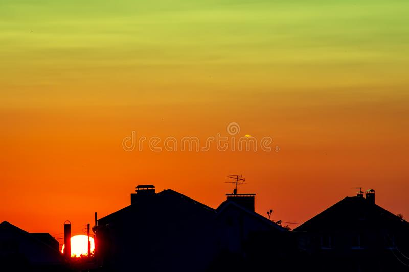Dark, clear silhouettes of the roofs of houses in the rays of the setting sun. Sunset in the city. Silhouette City landscape in royalty free stock image