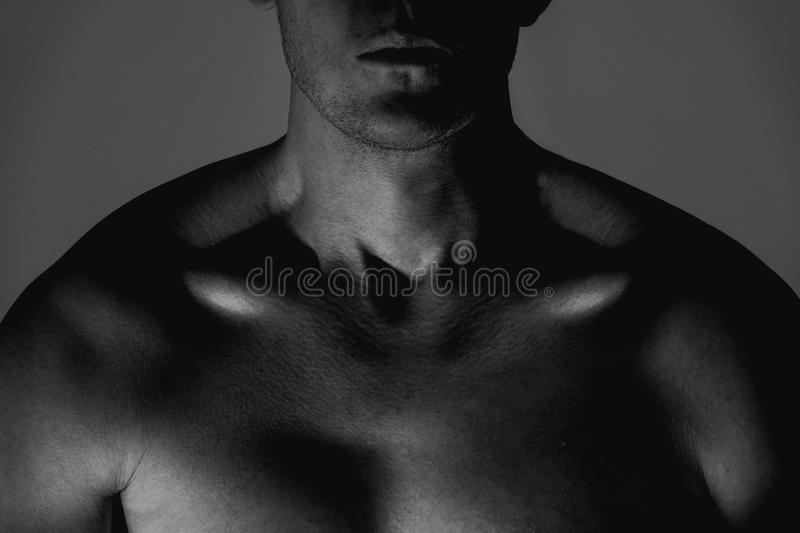 Dark close up studio shoot of strong masculine athletic man. royalty free stock photo