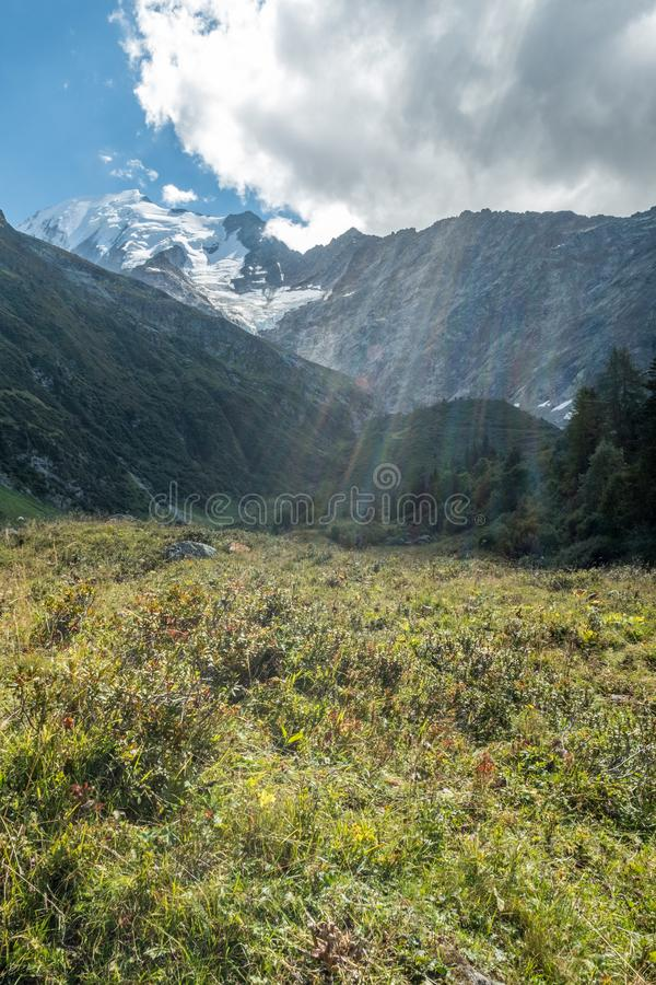 Dark cloud allows radiating sunbeams to brighten meadows, Bionassay, France. As a cloud moves over the Mont Blanc massif, sunbeams radiate colorful light down stock photos