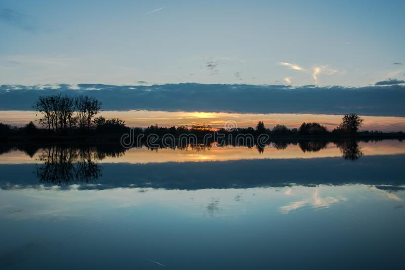 A dark cloud reflecting in the lake during sunset. And trees on the shore royalty free stock photography