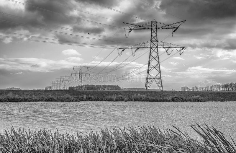 Dark clouds above a row of power pylons stock photo