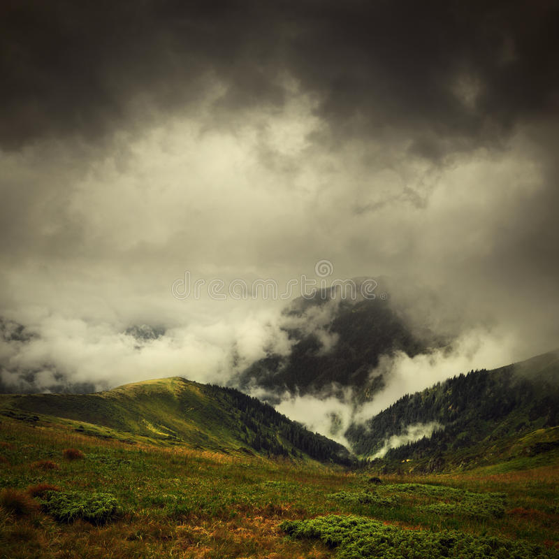Dark clouds and fog over mountain valley stock images