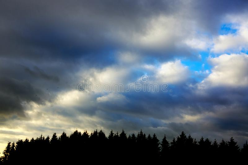 Dark gray dramatic sky with large clouds and sunlight. royalty free stock photography