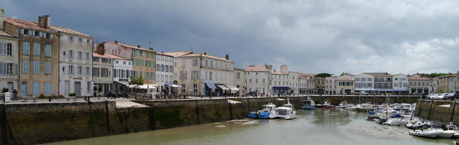 Dark clouds in harbour in St Martin de Re, Il de Re. Panoramic. Storm clouds over Saint Martin de Re, Il de Re, South West France. Harbour side. boats in water stock photography