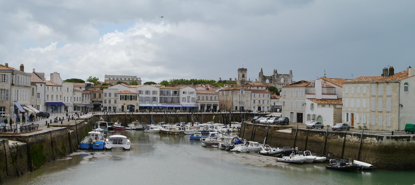 Dark clouds in harbour in St Martin de Re, Il de Re. Storm clouds over Saint Martin de Re, Il de Re, South West France. Harbour side. boats in water. Historic stock photo