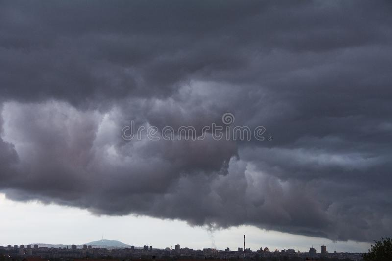 Dark clouds over the city. Dark cloud over the big city before the rain in late spring afternoon royalty free stock image