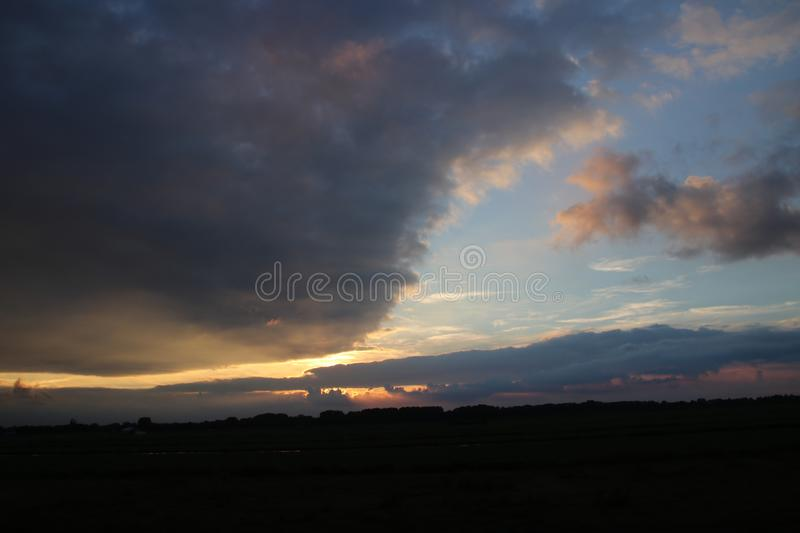 Dark clouds with several sunbeams during sunset in colorful sky in the Netherlands royalty free stock images